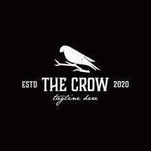 The Crow Logo Is Perched On A Dried Tree Branch