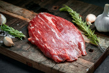 Raw Flank Beef Steak And Ingredients For Cooking On A Wooden Board, Close Up