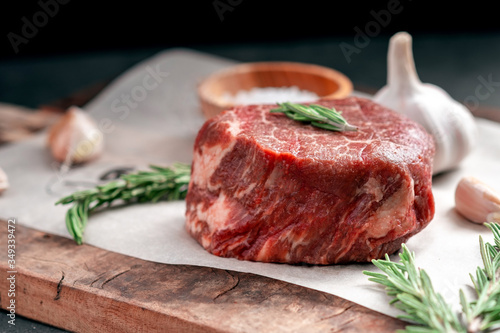 Fototapeta Prepared for grilling Raw steak filet Mignon beef on a wooden table with herbs obraz