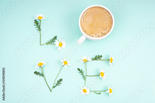 Creative romantic composition forming the word LOVE of chamomile flowers and a coffee cup on a light blue background. Vivid and tender fresh cup of love concept. Relationship refreshment idea.