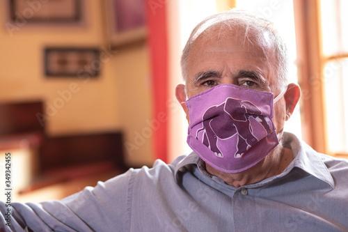Fotografie, Obraz Uomo anziano con mascherina protettiva divertente guarda serio seduto nel divano di casa