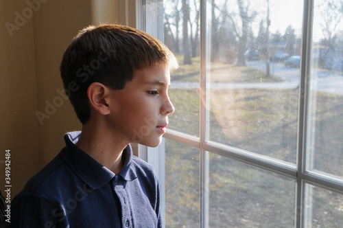 Young boy looking out thw window Canvas-taulu