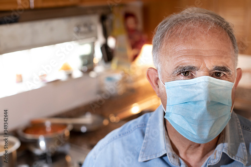 Ritratto di uomo anziano con mascherina protettiva e camicia in jeans da dentro Fototapeta