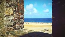Scenic View Of Beach Seen Through Stone Wall Window