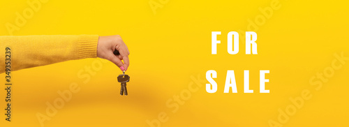 Fotomural female hand holding house keys over yellow background, inscription  for sale, pa