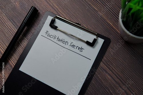 Facilitation Secrets write on paperwork isolated on wooden table. Wallpaper Mural