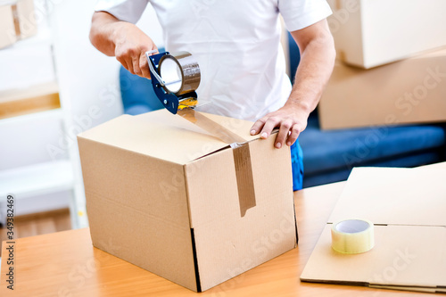 Fototapeta Worker hands holding packing machine and sealing cardboard or paper boxes obraz