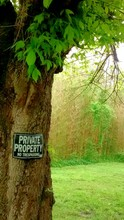 Private Property Sign On Tree Trunk In Field