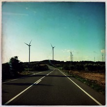 Asphalt Empty Country Road Along Landscape With Wind Turbines In Background