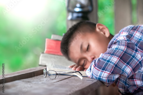 Close up eye glasses with boy resting after reading the Bible on wooden table, Christian concept Canvas-taulu