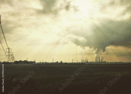 Distant View Of Factory Against Cloudy Sky Fototapete