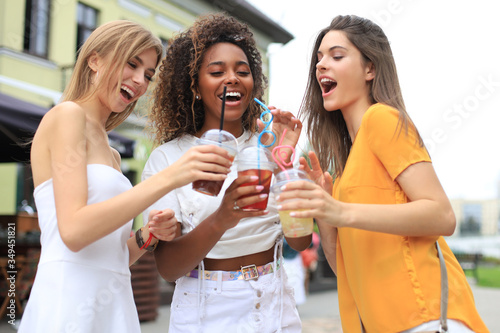 Foto Three trendy cool hipster girls, friends drink cocktail in urban city background