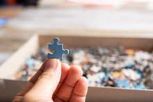 A Closeup View Of A Hand Holding One Piece Of Blue Jigsaw Puzzle Near A Cardboard Box Full Of The Rest Of The Pieces.