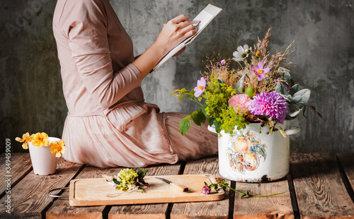 Valokuvatapetti female artist draws a composition of wild flowers in a pot in a rustic style, a sketchbook on a table with pencils