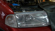 Close up car headlight with opened hood. Enginge repair in a car service.