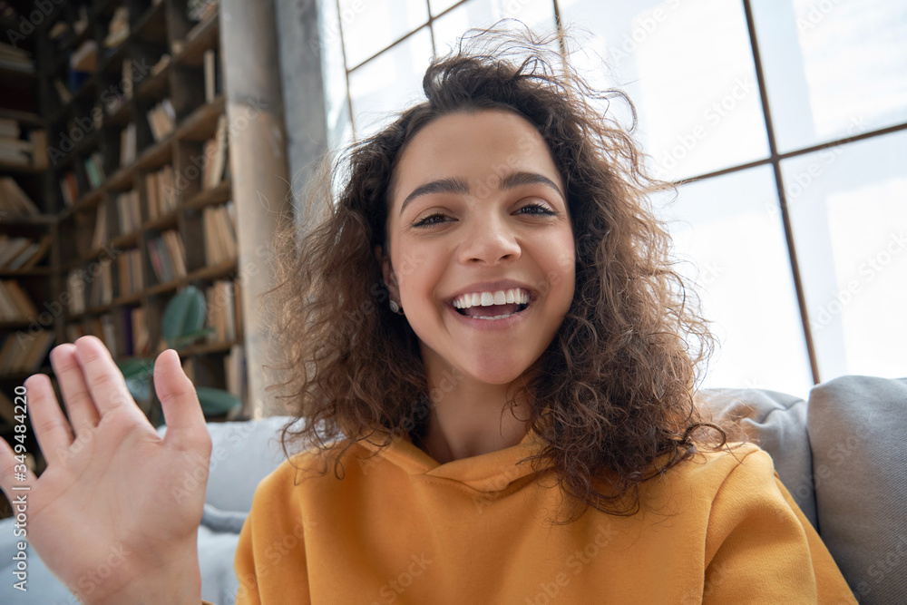 Fototapeta Happy hispanic latin gen z teen girl blogger smiling face waving hand talking to webcam recording vlog, social media influencer streaming, making video call at home. Headshot portrait. Webcamera view