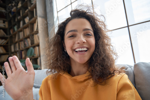 Fototapeta Happy hispanic latin gen z teen girl blogger smiling face waving hand talking to webcam recording vlog, social media influencer streaming, making video call at home. Headshot portrait. Webcamera view obraz