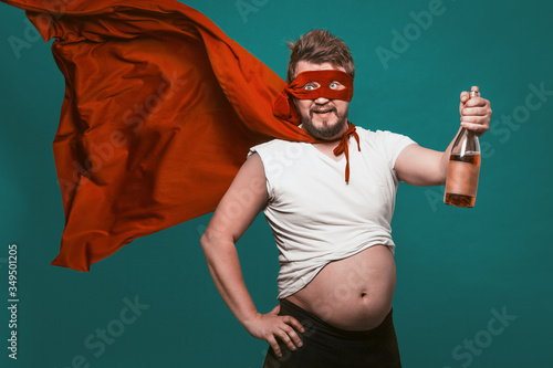 Fotografie, Tablou Drunk Superhero Or Antihero Man With Bottle Of Alcohol, Man In Superhero Red Mas