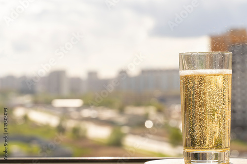Fototapeta glass with soda close up on a blurred urban background. a lot of playful bubbles fill the glass, backlight. space for text on the left, copy space obraz