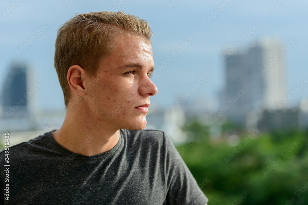 Fototapeta Closeup profile view of young handsome man with blond hair outdoors