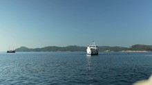 Large Ferry Approaching Port On A Clear Sunny Day With Land Behind.