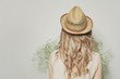 Beautiful blonde woman with curly hair wearing a summer hat, female back