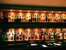 Liquor Bottles Arranged On Shelf In Bar