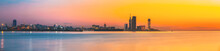 Batumi, Adjara, Georgia. Skyline Of Resort Town At Sunset Sunrise. Bright Orange Evening Sky. View From Sea To Cityscape With Modern Urban Architecture, Skyscrapers And Tower. Golden Hour. Panorama