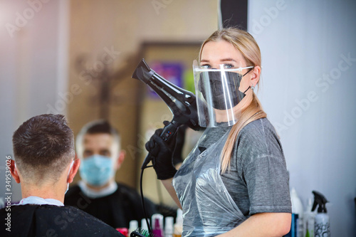 Obraz A hairdresser with security measures for Covid-19 holding a hairdryer and looking at the camera in a medicine mask, social distance, cutting hair with a medical mask, eye mask and  gloves - fototapety do salonu