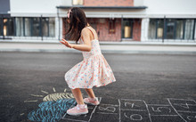 Image Of Cute Little Girl Playing Hopscotch On Playground Outdoors. Pretty Child Plays Next To The House Oustside. Kid Plays Hopscotch Drawn On Pavement. Summer Activities And Games For Children.