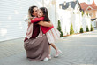 canvas print picture - Outdoor image of the mother embrace her little girl going back at home from the school. Happy daughter hugs her mom feels happy after the preschool day. Woman hug her child next their house outside.