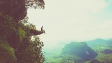 Man Sitting On Cliff By Sea Against Sky