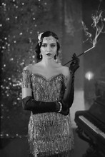 Artwork Portrait Young Flapper Retro Beautiful Woman. Mouthpiece In Hand Cigarette Smoke. Backdrop Shine Brilliant Bokeh Classic Room. Black And White Old Photo. Wave Hairstyle. Fashion Style 1920s