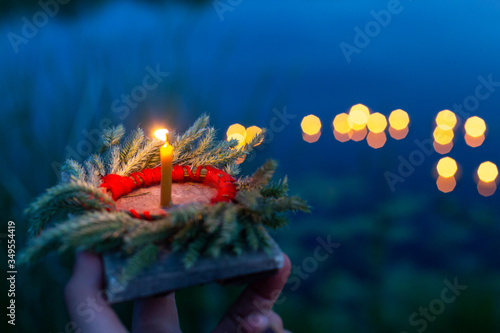 Fototapeta A hand holds a wreath and a fire on a Board close-up, a mysterious ancient Slavi