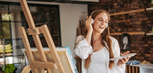 Billede på lærred Smiling young lady listening to music and painting picture, enjoying art therapy
