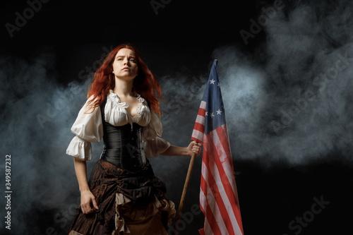 Fototapeta Girl in historic dress from United States Revolutionary War with flag