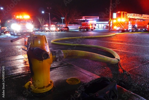 Fotografiet Pipe Connecting Fire Hydrant By Emergency Vehicles On Street At Night