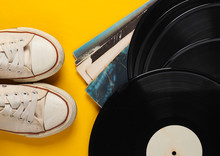 Vinyl Record Albums And Retro Sneakers On Yellow Background. Top View