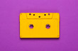 canvas print picture - Yellow audio cassette on purple background. 80s. Top view