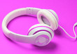 canvas print picture - Classic white wired headphones on neon pink paper background. Retro style. 80s. Pop culture. Music lover