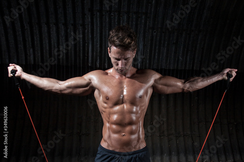 Stampa su Tela Macho Man Exercising With Resistance Bands Against Corrugated Iron