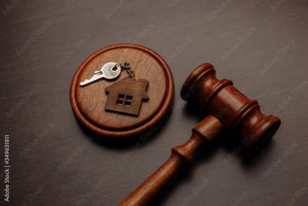 Fototapeta Judge gavel and key chain in shape of two splitted part of house on wooden background. Concept of real estate auction or dividing house when divorce, division of property, real estate, law system.