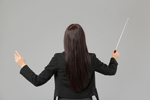 Young Female Conductor On Grey Background