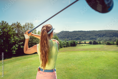 Woman with driver on golf course at the tee