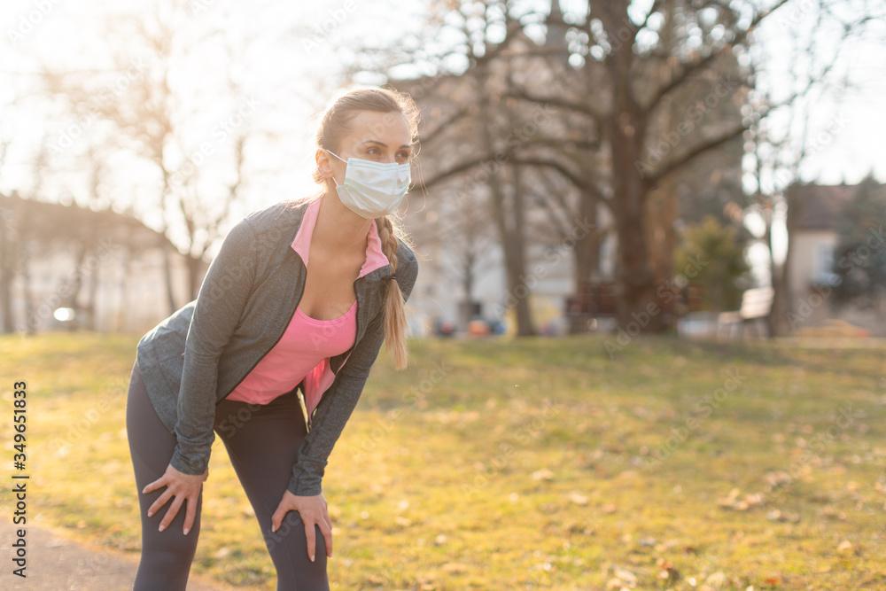Fototapeta Fit woman during covid-19 crisis having break from running