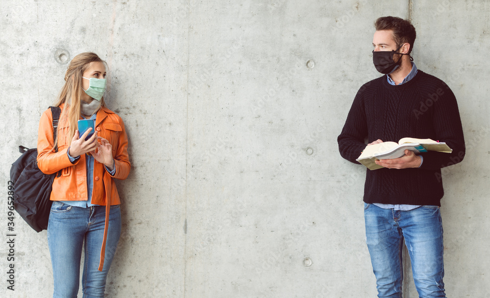 Fototapeta Two students standing in social distance wearing face mask