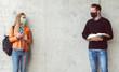 Leinwandbild Motiv Two students standing in social distance wearing face mask