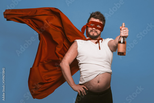 Tablou Canvas Tipsy superhero or antihero holds bottle of wine, man in superhero red mask with