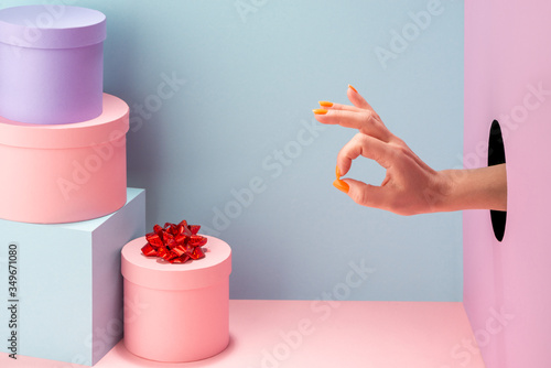 Fotografía Woman's hand showing an alright sign on blue and pink background