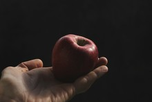 Cropped Hand Of Man Holding Apple Against Black Background